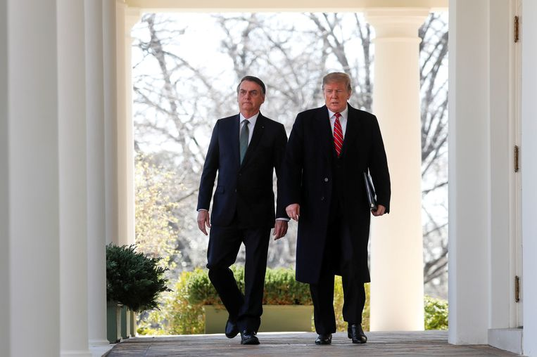 Donald Trump en Jair Bolsonaro op weg naar een persconferentie na een ontmoeting in maart vorig jaar in het Witte Huis. Beeld REUTERS