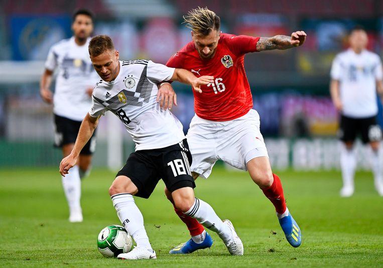 Peter Zulj (R) in duel met Joshua Kimmich (L) in een oefenpot tussen Oostenrijk en Duitsland.