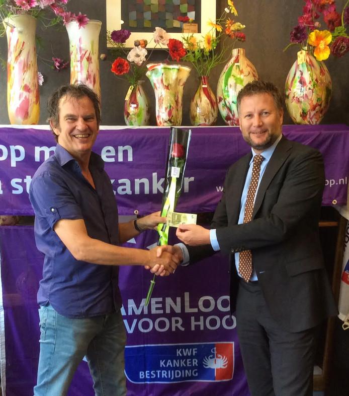 Burgemeester Martijn Dadema koopt de eerste roos van bloemist Peter Veldmaat, die een ware stormloop verwacht.