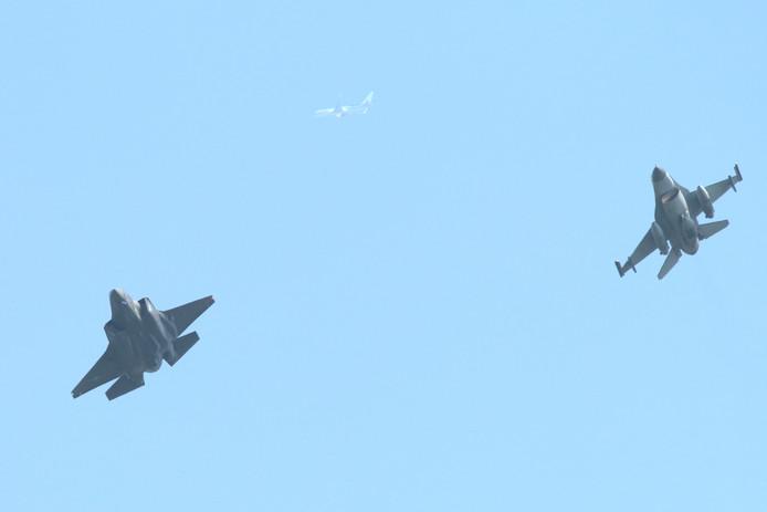 """De """"oude"""" F16 begeleidt de gloednieuwe F35 tijdens haar rondvlucht boven Middelburg met een TUI Boeing op de achtergrond."""