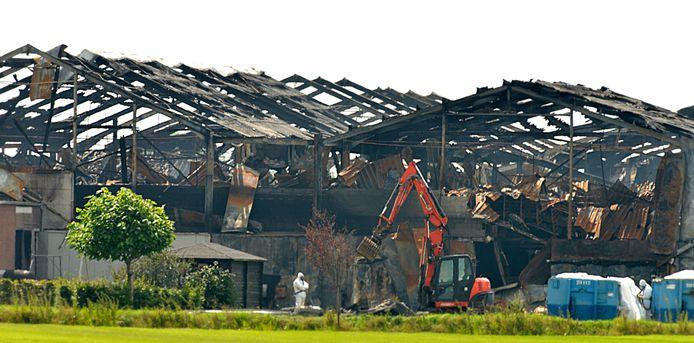 Opruimen van de ravage na de stalbrand in Erichem.