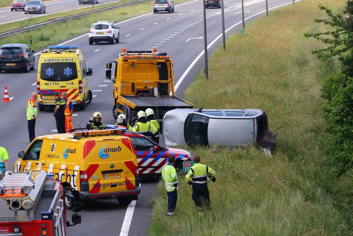 Een auto belandde naast de A50 bij Schaijk op zijn kant.