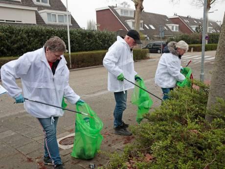 Vrijwilligers gewapend met grijpers door straten van Waterland