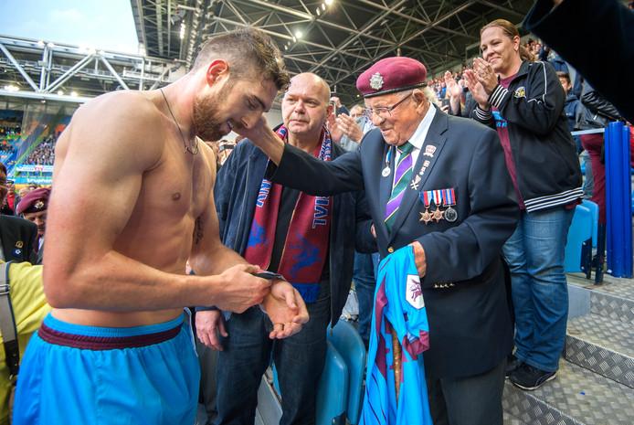 Paul Koster (midden) kijkt toe hoe Airborne-veteraan Little Joe het wedstrijdshirt van Vitesse-aanvoerder Guram Kashia krijgt na de Airborne-wedstrijd in 2015.