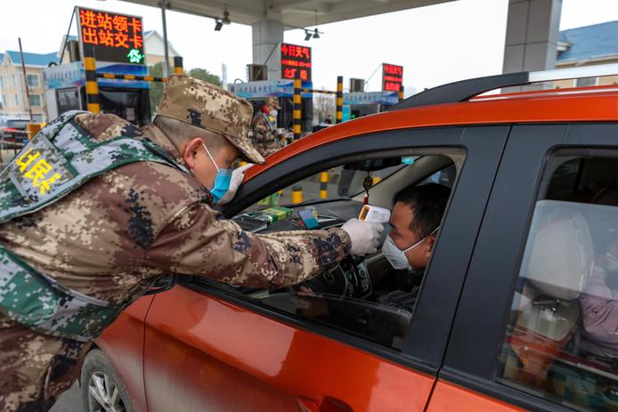 Een militair checkt de lichaamstemperatuur van een automobilist bij een tolpoort op een snelweg bij Wuhan, het epicentrum van de virusuitbraak die in China voor veel onrust zorgt