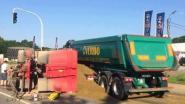 Oplegger met zand kantelt tegen vrachtwagen
