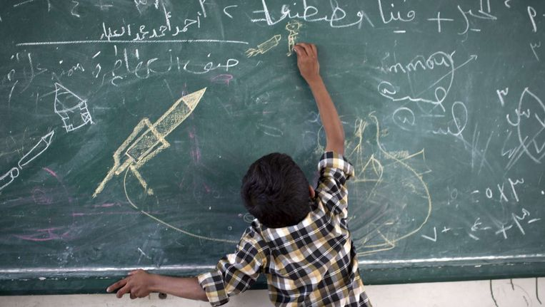 Een Palestijns jongetje tekent op een bord van een VN-school. Beeld afp