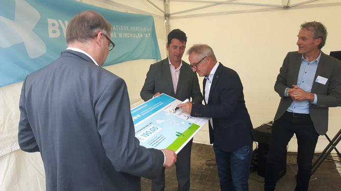 Met een handtekening werd de koop bezegeld. (Wethouders Jan Hoskam en Eric Logister houden het bord vast) Voorzitter Joep Mol (rechts) kijkt toe