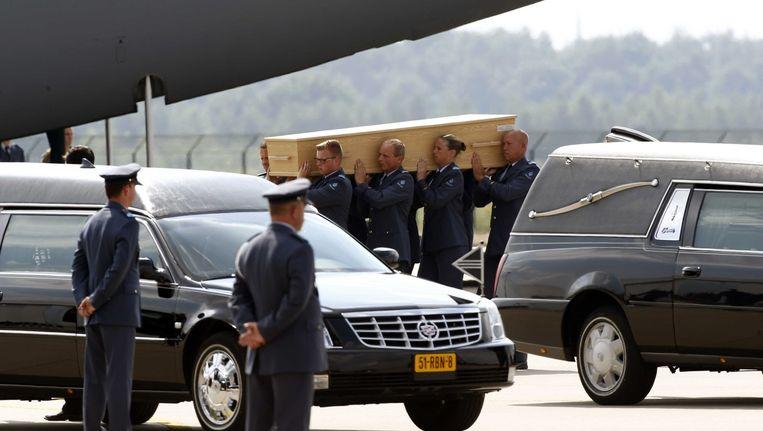 Soldaten dragen de lichamen van voorlopig de laatste slachtoffers van de vliegramp die vandaag in Eindhoven zijn aangekomen. Beeld epa