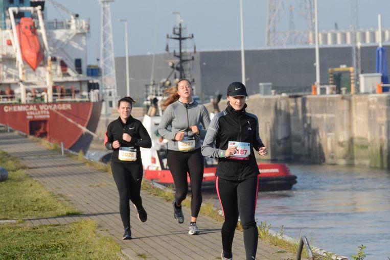 De deelnemers liepen door natuurgebieden met de haven op de achtergrond.