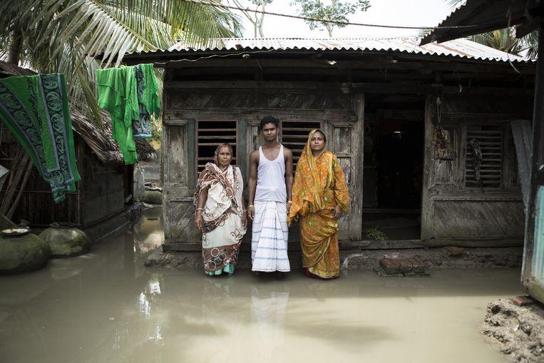 Familie in een overstroomde wijk in Mongla, Bangladesh. Beeld Mike Roelofs