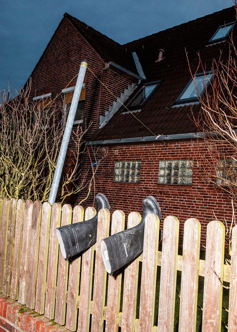 Laarzen hangen uit op het tuinhek van de familie Kruse. Beeld Hilde Harshagen