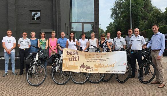 Johan Museeuw (uiterst links op de foto) kwam langs bij de politiezone Regio Tieltmet een presentje voor enkele van de deelnemers van de provinciale campagne 'De testkaravaan komt eraan'.