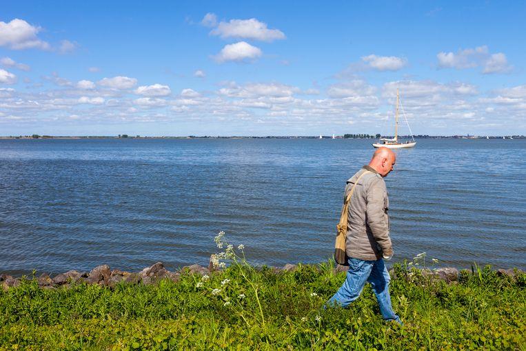 Bioloog  Ingo Janssen op ringslangenjacht bij Marken. Beeld Renate Beense