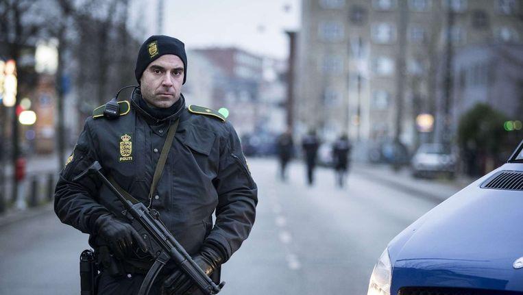 Een politie-agent bewaakt de straat rond het Noerrebro-station, waar de politie de vermoedelijke dader van de twee dodelijke aanslagen in Kopenhagen uitschakelde. Beeld ANP