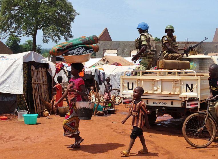 Een vrouw en kind passeren een VN-vredesmacht in Bria in de Centraal Afrikaanse Republiek (CAR).  Beeld AFP