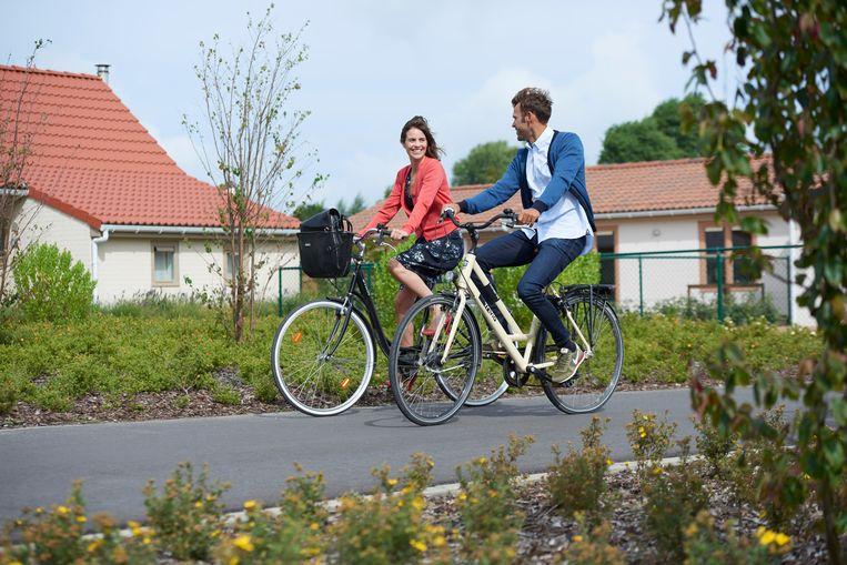 In vakantiepark Duinenwind kan je doen waar jij zin in hebt, zoals een lekker fietstochtje maken. Op de achtergrond zijn de vakantiehuizen te zien.