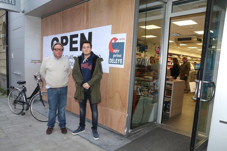 Zaakvoerder en gedupeerde Rik Durnez met zijn zoon bij de plank die zijn winkel afsluit.