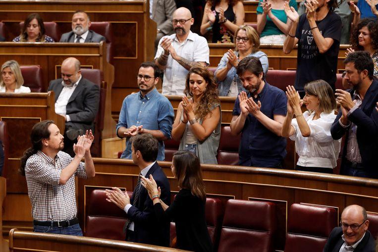 Podemos-leider Pablo Iglesias (links) krijgt na zijn toespraak applaus van zijn partijgenoten in het parlement. Een historische linkse coalitie met de sociaal-democratische PSOE komt er voorlopig niet, zo bleek donderdag.  Beeld EPA