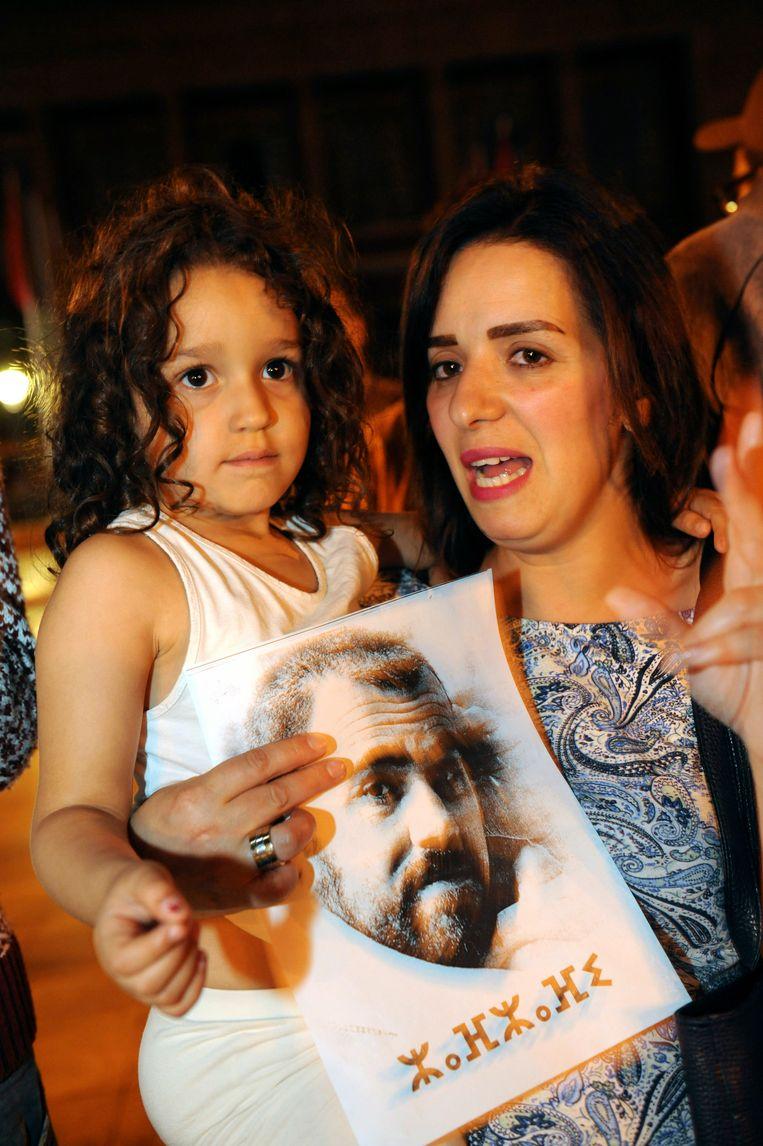 Een betoger en haar kind houden een foto vast van Nasser Zafzafi.