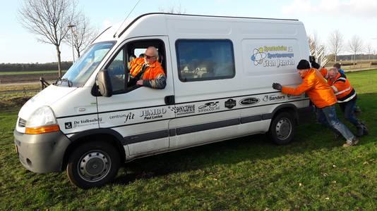 De bus met de aanhanger vol dranghekken voor de pitstraat van het NK veldrijden in Huijbergen, met Stan Jansen aan het stuur, moet even worden geduwd omdat de wielen doorslippen op het natte gras.
