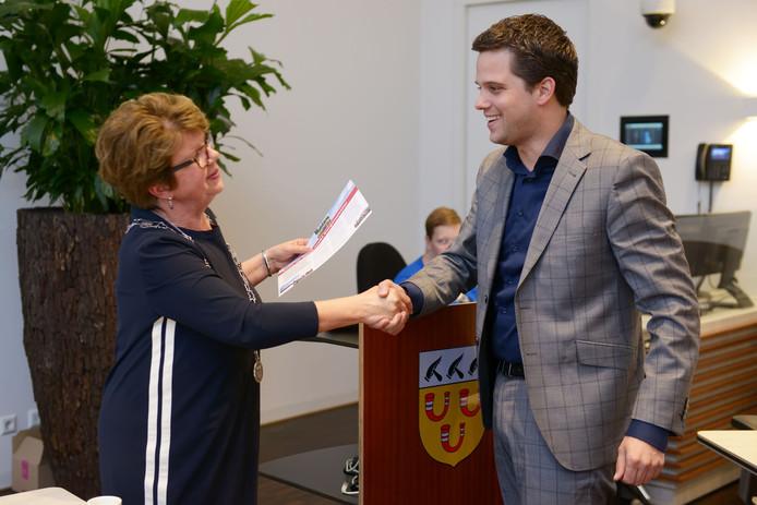 Voorzitter Frank van Wel van de vertrouwenscommissie overhandigt de profielschets aan Loes Heijs.