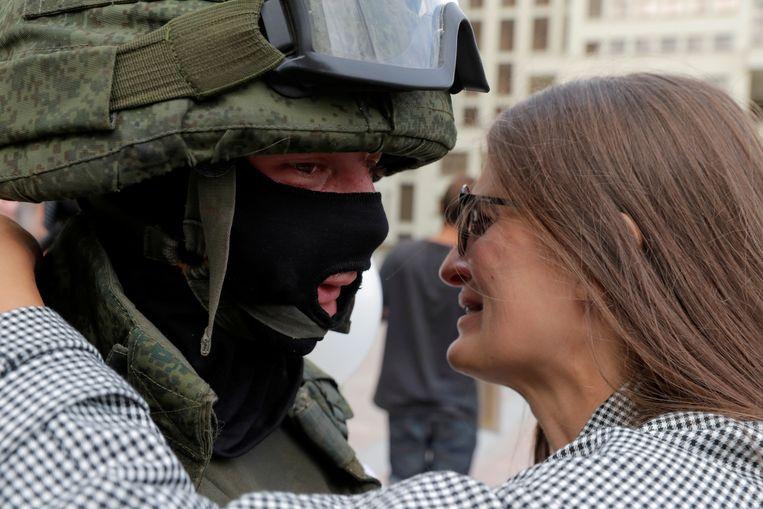 Een demonstrant omhelst een Belarussische militair. Beeld REUTERS