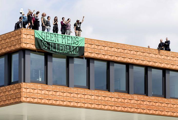 Actievoerders op het dak van het NAVO-gebouw aan de Waalsdorperweg in Den Haag