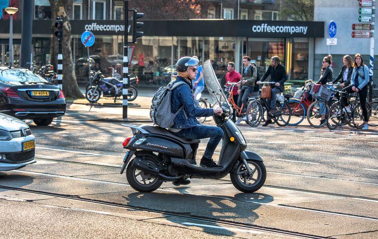 Snorfietsers moeten in Amsterdam voortaan op de rijbaan rijden, met een helm op Beeld null
