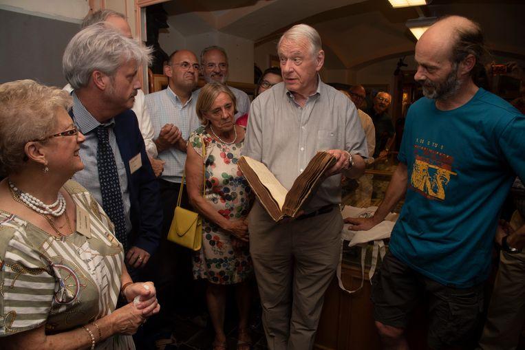 De Heemkring schenkt een 240 jaar oud register aan het Kerkarchief. Oud burgemeester Marc Gybels en voorzitter Kerkfabriek neemt het graag in ontvangst.