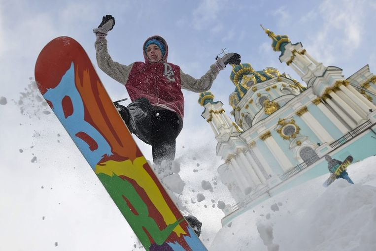 Het is niet alleen kommer en kwel in Kiev, een snowboarder porbeert te spingen op het plein voor de Andreevskayakerk Beeld anp
