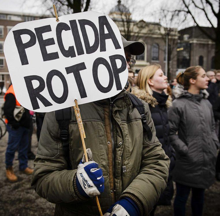 Demonstranten tijdens de tegendemonstratie van de SP tegen Pegida met de boodschap: vluchtelingen zijn welkom en racisme niet. Beeld ANP