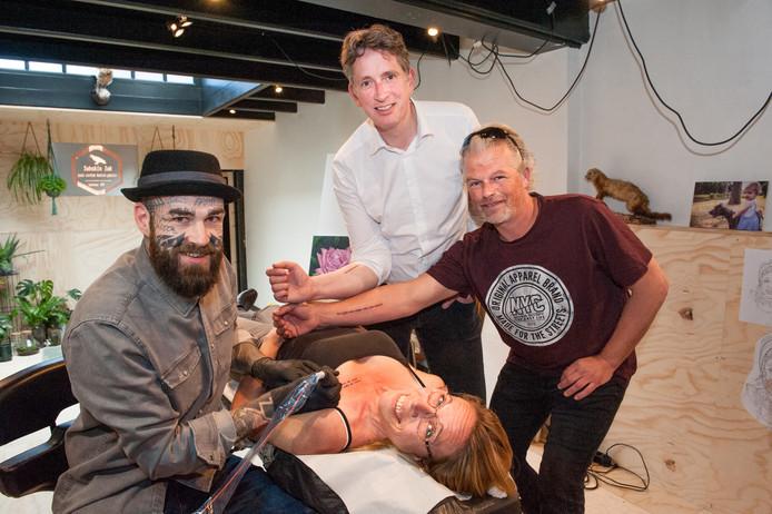 Sandra Hofman, Pieter Stroop van Renen (midden) en Robin Stalman dragen een dichtregel op hun huid.