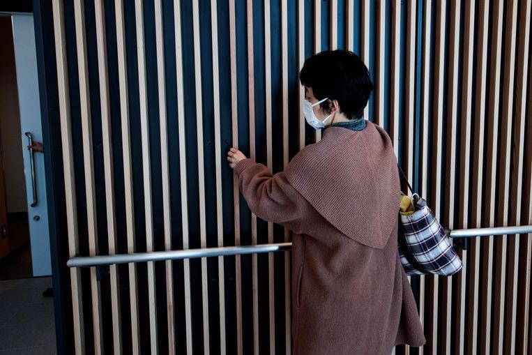 Een vrouw in Tokio bestudeert het exterieur van de Ariake Arena die deze week werd geopend. In de hal worden tijdens de Spelen en Paralympics volleybal and rolstoelbasketbal gehouden.  Beeld AFP