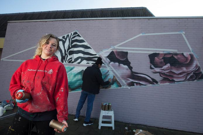 Rosalie de Graaf beschildert een blinde muur op sporthal Beumerskamp in Doesburg.