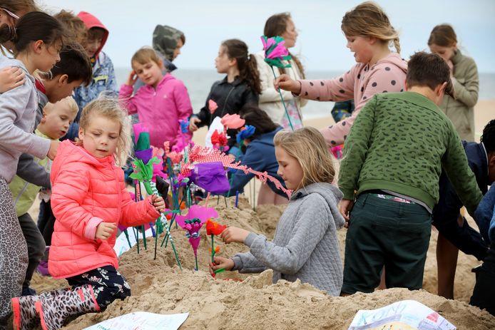Kinderen met strandbloemen op het strand.