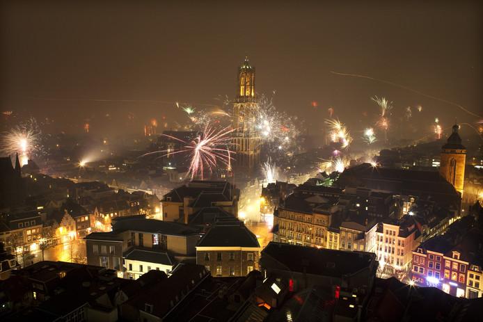 De Domtoren in Utrecht wordt door vuurwerk verlicht tijdens nieuwjaarsnacht.