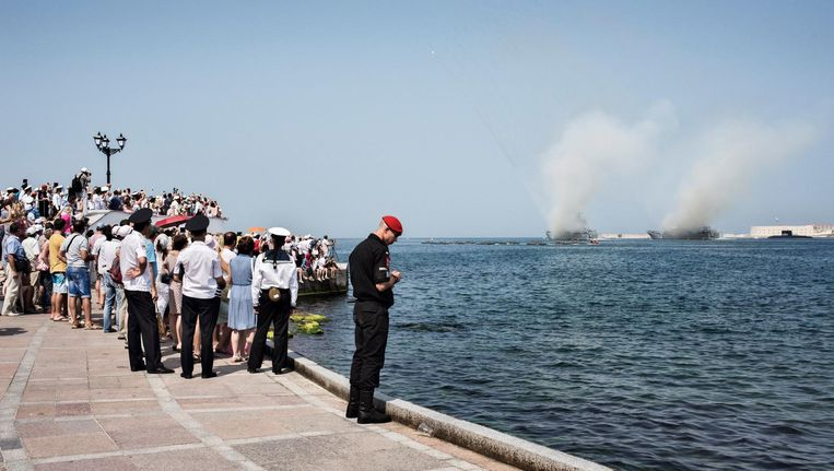 Op een kade van Sebastopol kijken toeschouwers hoe oorlogsschepen torpedo's afvuren tijdens de vlootschouw zondag. Beeld Yuri Kozyrev/ Noor