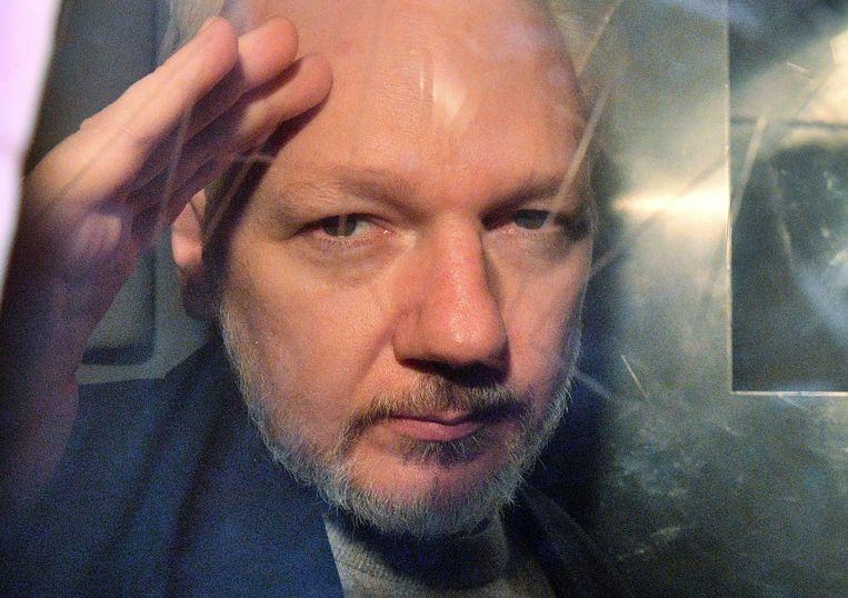 Julian Assange door het raampje van het gevangenisbusje waarmee hij door Londen werd gereden.  Beeld AFP