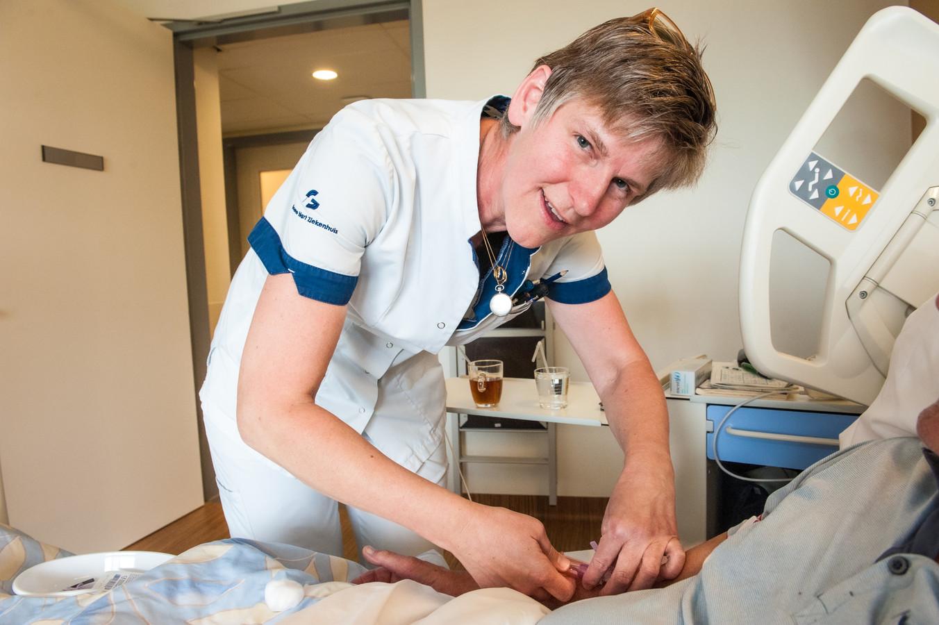 Martine Stöcker neemt bloed af bij een patiënt. Even later zal zij het analyseren in het ziekenhuislaboratorium.