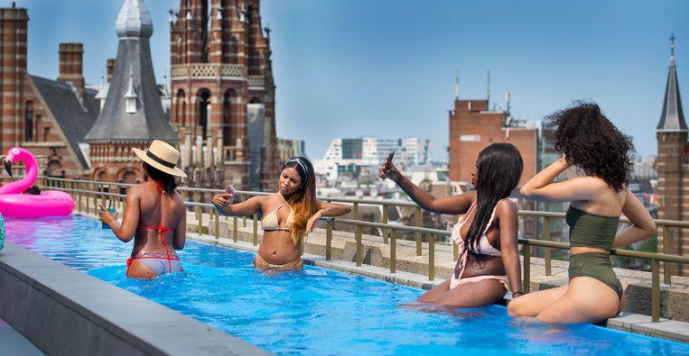 Toeristen zoeken verkoeling in het zwembad van vijfsterrenhotel W Amsterdam.  Beeld Hollandse Hoogte / ANP