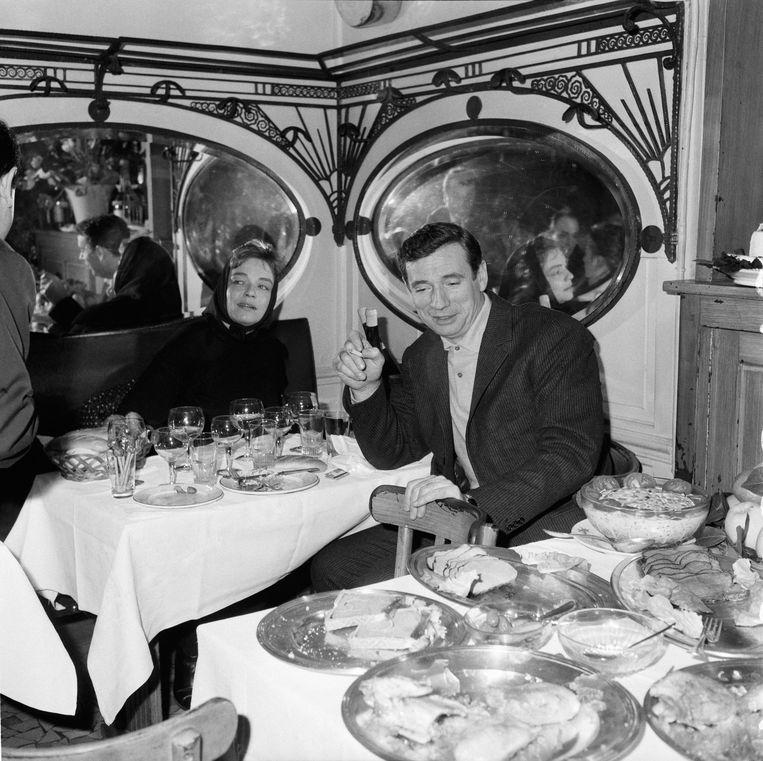 Simone Signoret op 42-jarige leeftijd met haar man Yves Montand in een restaurant in Parijs, 1963. Beeld Getty Images