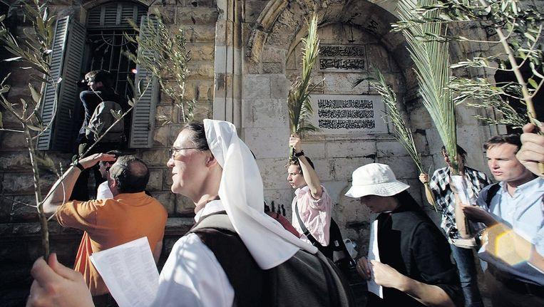 Een non en een groep toeristen lopen door de Oude Stad van Jeruzalem met Palmpasen. Beeld EPA