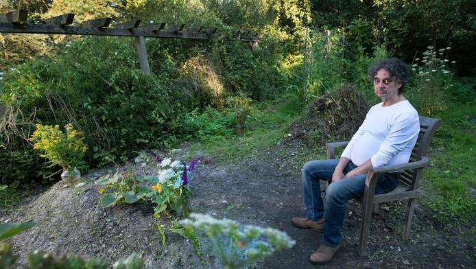 Frenk Windels naast het graf van zijn overleden echtgenote in zijn eigen achtertuin in Brunssum.