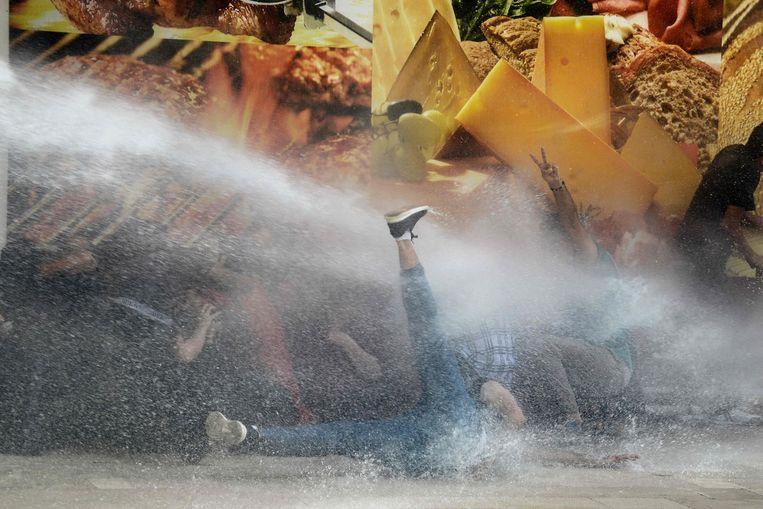 Demonstranten die protesteren tegen het afzetten van burgemeesters in drie Koerdische steden worden maandag in Diyarbakir getroffen door een waterkanon. Beeld AFP