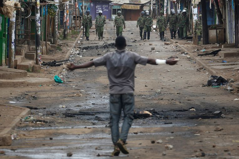 Een aanhanger van oppositieleider Raila Odinga  loopt richting de Keniaanse oproerpolitie in Kibera, een sloppenwijk van Nairobi. Beeld EPA