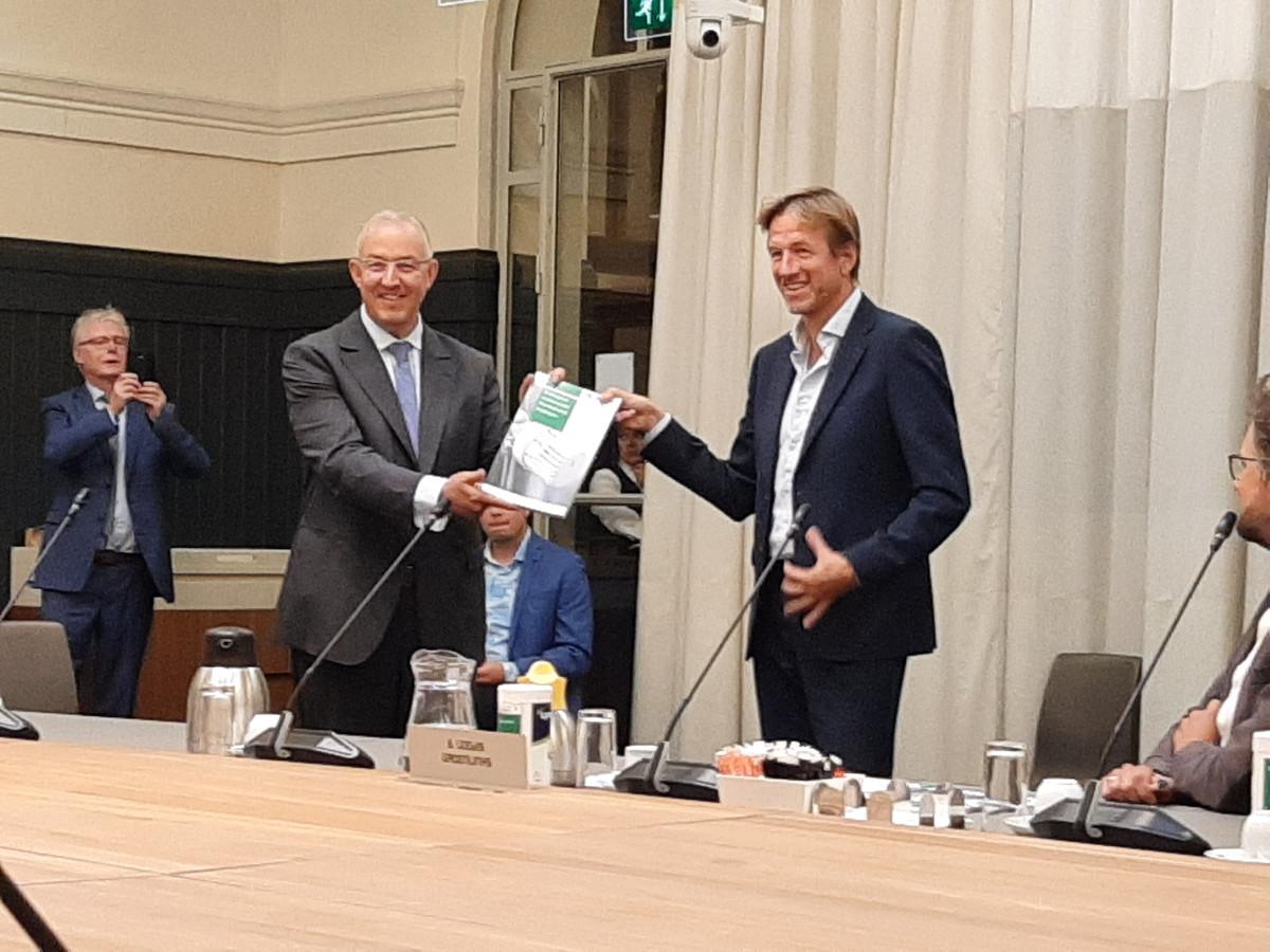 VVD-raadslid Jan-Willem Verheij, voorzitter van de enquêtecommissie Warmtebedrijf, overhandigt het eindrapport aan burgemeester Aboutaleb.