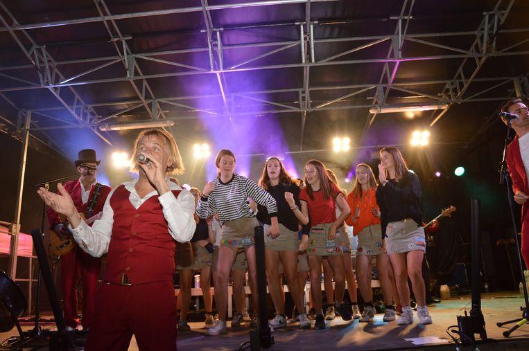 Charel van Domburg (bekend van The Magical Flying Thunderbirds) daagt de meisjes van de chiro uit voor een danswedstrijd tegen het publiek tijdens de 21 juli-viering.