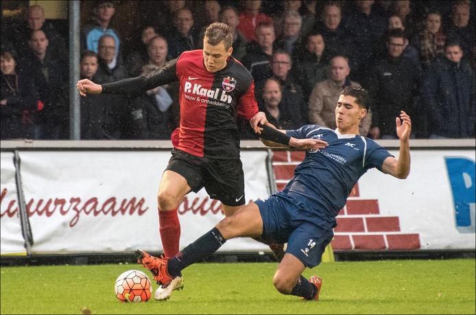 JVC'er Ilias Zaimi probeert met een uiterste krachtsinspanning De Treffers-verdediger Frenk Keukens van de bal te krijgen.