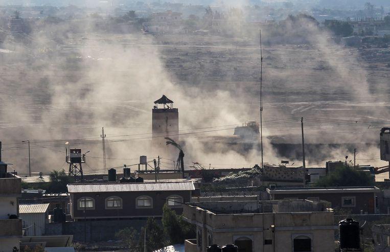Een Egyptische grenstoren aan de zuidgrens van de Gazastrook te midden van stof, veroorzaakt door graafmachines die tunnels proberen bloot te leggen.   Beeld AFP